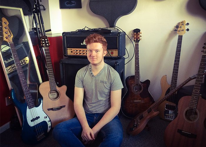 guitarist sat with amplifiers and guitars